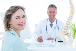 39828266 - patient and doctor smiling at camera in medical office