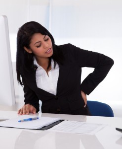 19632371 - young businesswoman sitting on chair and holding her back in pain