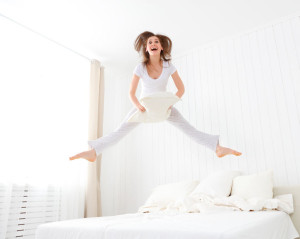 51559684 - funny happy girl jumping and having fun in bed